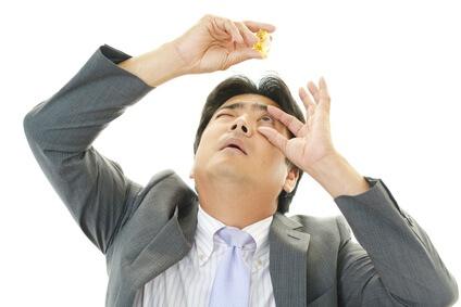 目薬をさす男性